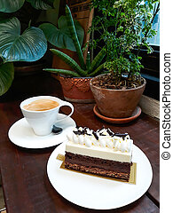 Chocolate cake with a cup of hot coffee on wooden table.