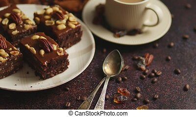 Chocolate cake with caramel frosting, pecans and hot coffee, on rustic background. Freshly baked homemade toffee cake with cup of coffee. Sweet dessert. Side view, flat lay.