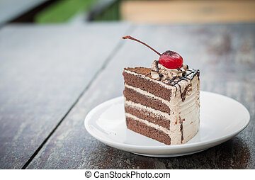 chocolate cake with cherry topping in cozy outdoor cafe