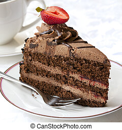 Chocolate cake topped with a strawberry, served with coffee.