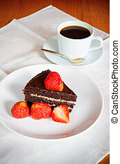 Chocolate cake with fresh strawberry and a cup of coffee. Selective focus on cake