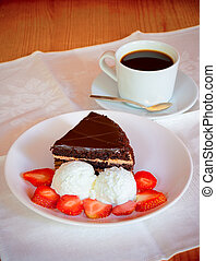 Chocolate cake with ice cream and cup of coffee. Selective focus on cake