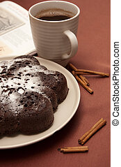 chocolate cake with icing sugar and a cup of coffee on a ...