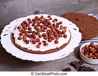 Chocolate cake with nuts on wooden background