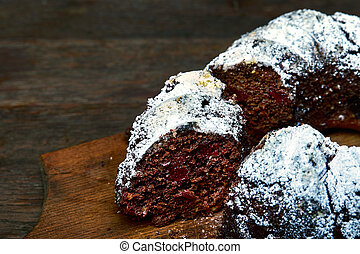 Chocolate cake with sour cherries and wallnuts on a wooden cutting board over rustic vintage background, selective focus