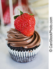 Chocolate cake with strawberries on the table.