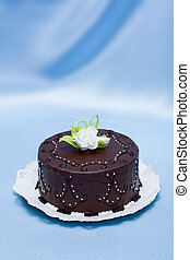 Chocolate cake with white edible candy rose decoration on blue silk background