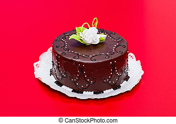 Chocolate cake with white edible candy rose decoration on red background