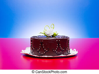 Chocolate cake with white edible candy rose decoration on red-blue background