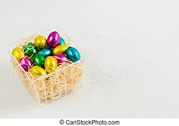 Chocolate candies easter eggs in plastic basket with copy space