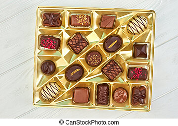 Chocolate candies in box, top view.