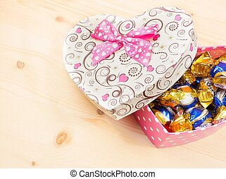 chocolate candies in gift box on wood table, concept of valentine day
