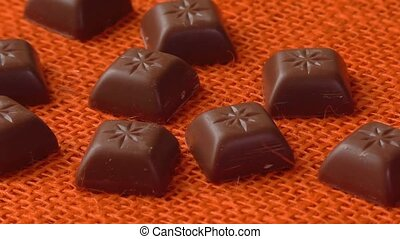 Chocolate candies over orange background