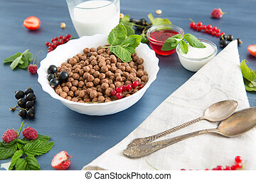 Chocolate cereal balls in bowl and milk. Selective focus Healthy tasty breakfast chocolate balls with strawberries, raspberries, black currants and red currants.