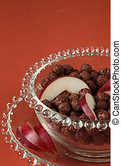 Chocolate cereals with slices of red apple