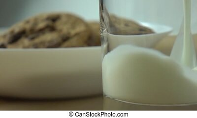 Chocolate chip cookies and milk being poured in a glass. Close up super slow motion shot