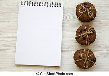 Chocolate chip cookies with notebook on a white wooden table, from above. Top view.