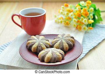 Chocolate cookie in red plate with flower and cup of tea.