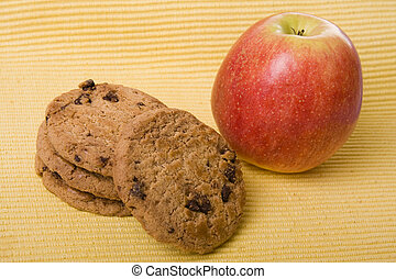 Chocolate cookies and a red apple on a yellow background