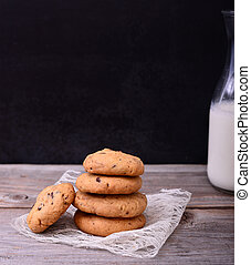 Chocolate cookies on lace napkin with bottle of milk in background on black table