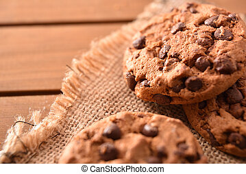 Chocolate cookies on sackcloth on wooden slatted table detail