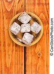 Chocolate cookies with coconut served on the plate over wooden background