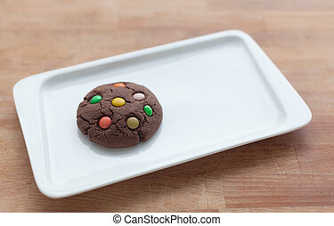 Chocolate cookies with colorful candy on a plate on a wooden boards background