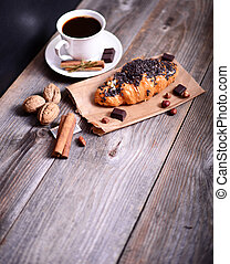 Chocolate croissant with coffee on table