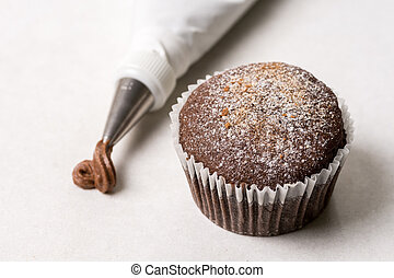 Chocolate cup cake with piping bag on the white marble ...