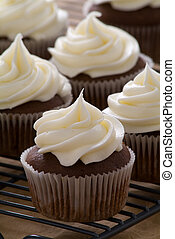 Fresh delicious gourmet chocolate cupcakes with vanilla frosting on a cooling rack.