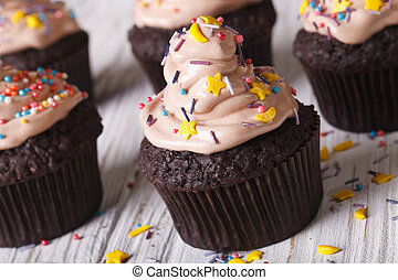 Chocolate cupcakes decorated with cream close-up. Horizontal