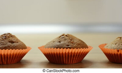Chocolate cupcakes in paper cups and a white cup on a wooden...