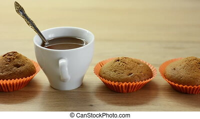 Chocolate cupcakes in paper cups and a white cup with coffee...