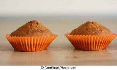 Chocolate cupcakes in paper orange cups on a wooden table.