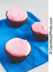 Chocolate cupcakes with pink cream on a blue napkin