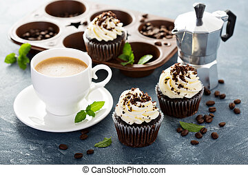 Chocolate cupcakes with vanilla frosting and a cup of coffee