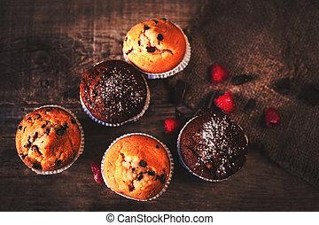 Chocolate dark muffins on wooden background with powdered...