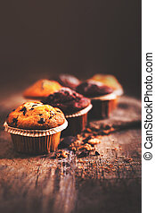Chocolate dark muffins on wooden table  close up with copy space