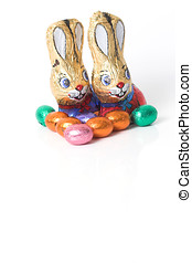 Chocolate easter bunnies with easter eggs on white...