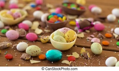 easter, junk-food, confectionery and unhealthy eating concept - chocolate eggs and drop candies on table