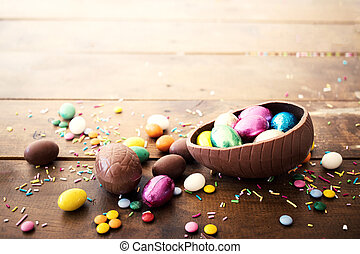 Chocolate easter eggs and sweet candies on wooden...