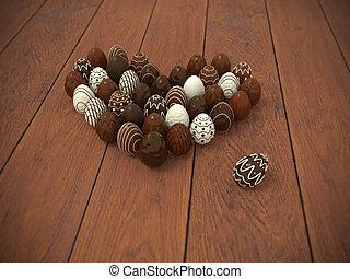 Chocolate Easter eggs heart on brown wooden floor -...