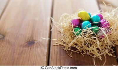 chocolate easter eggs in straw nest on table