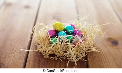 chocolate easter eggs in straw nest on table - easter,...