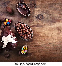 Chocolate Easter eggs on wooden background with ribbon bow...