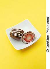 Chocolate egg (Easter egg) coconut stuffed with strawberry sliced in half on a plate. Isolated on yellow background. Copy space. Vertical shot