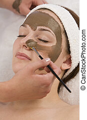 Chocolate Face Mask - A beautiful young brunette woman...