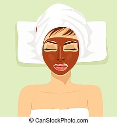Chocolate facial mask. Chocolate therapy. Young woman with treatment mask on her face at spa salon