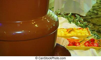 Chocolate flow. Fountain cascades hot chocolate. - Chocolate...