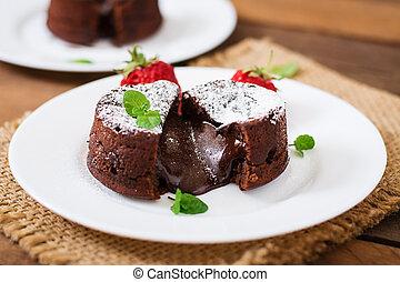 Chocolate fondant (cupcake) with strawberries and powdered...